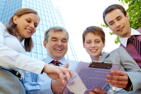 Below angle of several successful partners discussing paper outdoors photo