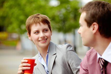 Portrait of happy business partners chatting during break outside at summer photo