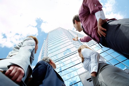 Below view of business partners pointing at modern office building against cloudy sky Stock Photo - 7088697