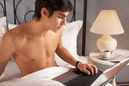 Young man sitting on bed and typing on laptop Stock Photo - 7088693