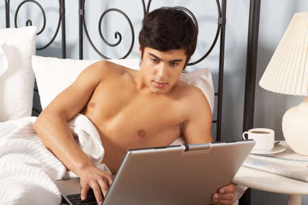 Young man lying in bed and typing on laptop Stock Photo - 7088686