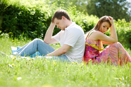 Photo of couple sitting back to back on grass outdoors