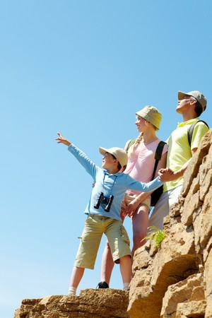 Portrait of family members looking afar while standing on cliff photo