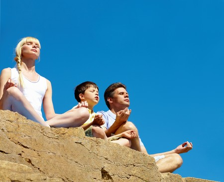 Photo of three family members sitting on cliff in pose of lotus on summer day photo
