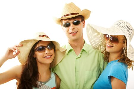 Portrait of happy man and girls in hats looking at camera through sunglasses Stock Photo - 7096000