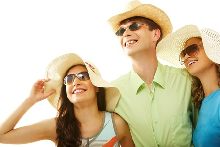 Portrait of stylish man and girls in hats looking upwards through sunglasses photo