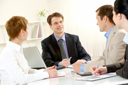 Portrait of businessman explaining work to his colleagues in office photo