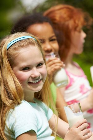 Portrait of cute girl drinking kefir outdoors with her friends on background Stock Photo - 7126019