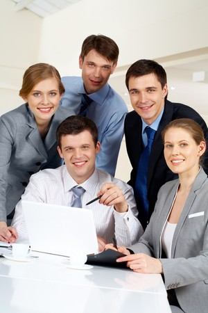 Portrait of several successful co-workers looking at camera with smiles at workplace photo