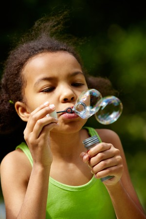 Portrait of cute girl blowing soap bubbles outdoors Stock Photo - 7147853