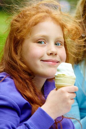 restful: Portrait of pretty girl eating ice-cream outside
