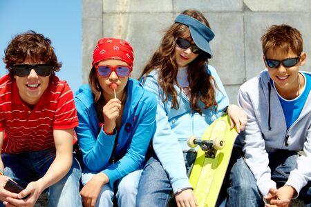 Row of several teens in sunglasses looking at camera photo
