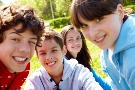 teen boy face: Portrait of happy teens looking at camera in the park at summer