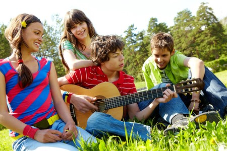 happy teenager: Portrait of handsome lad playing the guitar surrounded by his friends