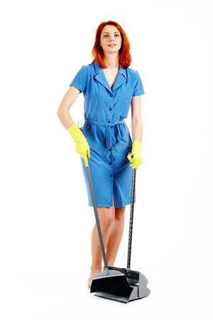 servicio domestico: Retrato del ama de casa agradable en t�nica azul barrer basura con pincel