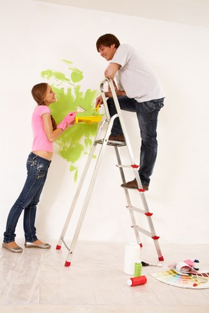 Affectionate couple helping each other to paint walls in new house photo