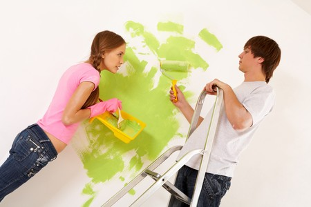 Industrious couple looking at each other while painting walls in new house photo