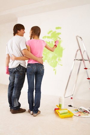 Rear view of embracing couple looking at each other while girl pointing at wall with green paint on photo