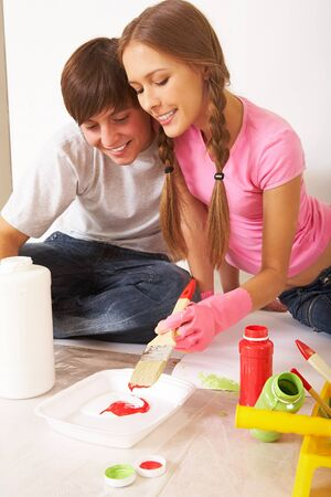 Photo of young couple mixing paints while sitting on floor in new flat Stock Photo - 7147840