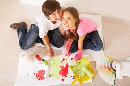Above angle of young couple mixing paints and looking at camera photo