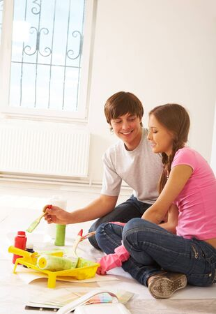 Photo of young couple speaking while mixing paints during flat improvement photo
