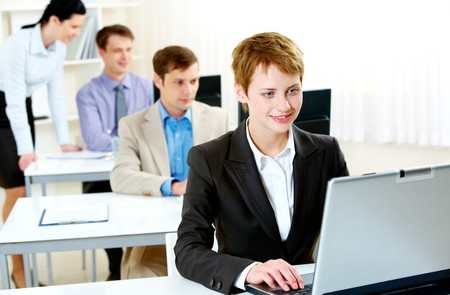 Portrait of business people typing on laptop during business training