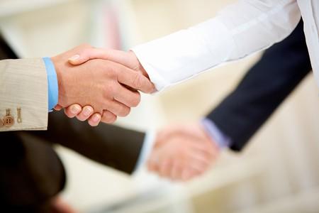manos estrechadas: Foto de dos handshakes de asociados de negocios