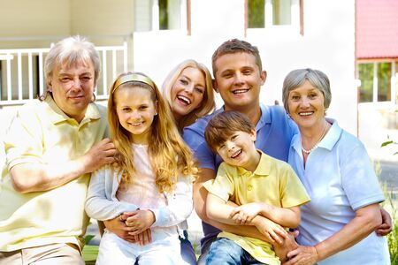 Portrait of senior and young couples with their children looking at camera outdoors by the house Stock Photo - 7179985