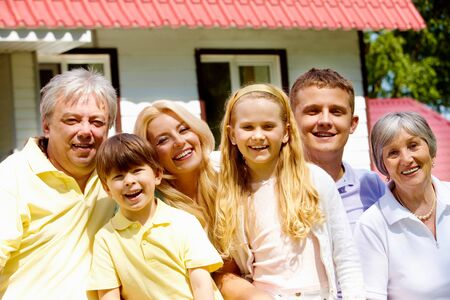 Portrait of senior and young couples with their children looking at camera outdoors by the house Stock Photo - 7200688