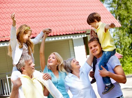 Portrait of happy senior and young couples having fun with children outdoors by their cottage Stock Photo - 7180194