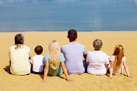 Photo of serene family members sitting on sandy shore and looking at blue water photo