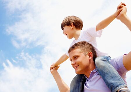 father and son: Portrait of happy man holding his son on neck on the background of sky