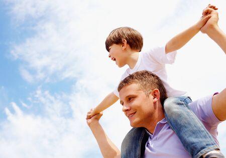 padre e hijo: Retrato de hombre feliz celebraci�n de su hijo en el cuello en el fondo de cielo Foto de archivo