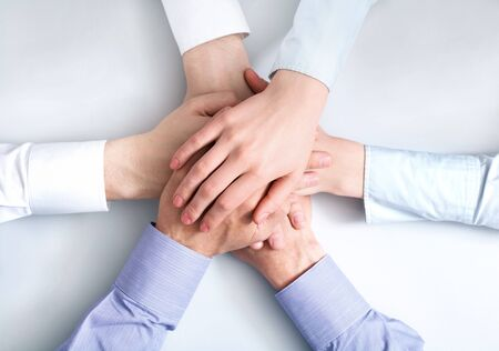 companionship: Above view of business partners hands on top of each other symbolizing companionship and unity