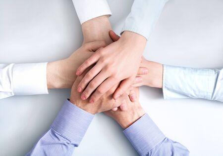 colaboracion: Por encima de la vista de las manos de asociados de negocios por encima de la otra que simboliza el compa�erismo y la unidad