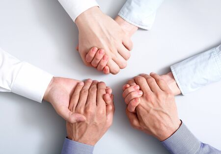consensus: Above view of business partners hands holding each other symbolizing support