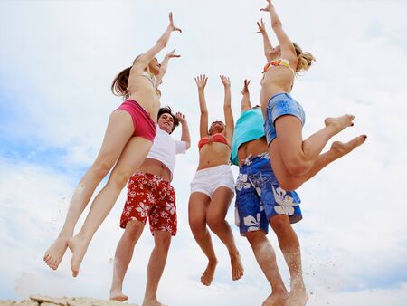 Photo of five friends in jump over sandy shore photo
