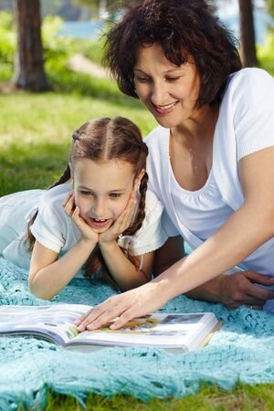 Portrait of mother and daughter reading in park on summer day photo
