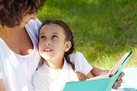 Portrait of curious girl looking at her mother while discussing book in park photo