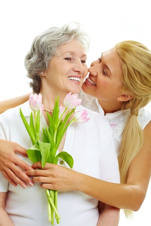 Portrait of pretty woman embracing her senior mother and holding tulips   photo