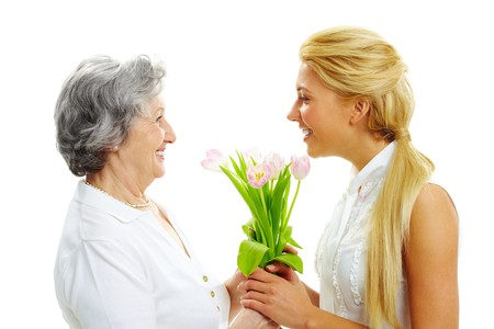 mature old generation: Portrait of young woman giving tulips to her mother    Stock Photo