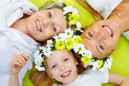 granddaughters: Portrait of grandmother, mother, girl with flowers lying on green floor Stock Photo