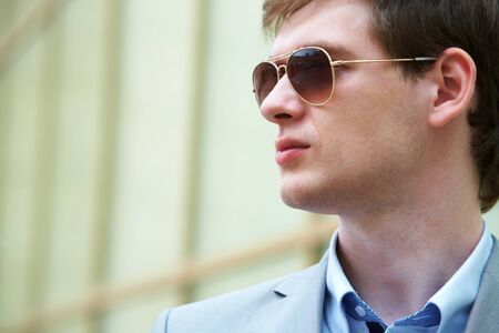 Handsome businessman looking through sunglasses outside photo