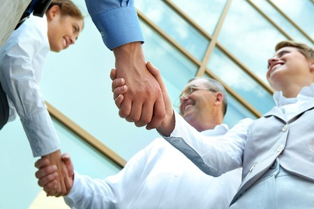 business deal: Below view of rows of happy partners handshaking outdoors on background of modern building Stock Photo