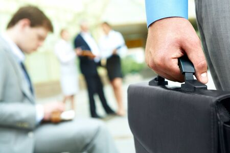 attache: Close-up of businessman hand holding briefcase in working environment