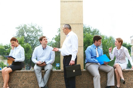 Image of several business partners interacting and working outside with papers photo