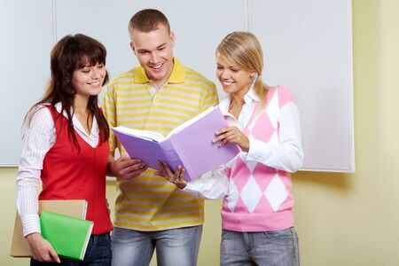 Portrait of three friends standing in classroom and discussing passage from book photo
