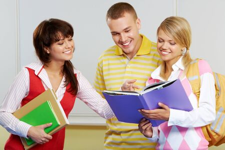 Portrait of three friends standing in classroom and discussing lessons photo