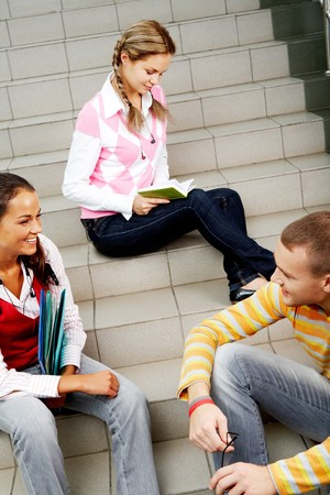 Image of friendly students chatting while sitting on stairs on background of reading girl photo