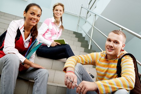 Portrait of three teens sitting on stairs and looking at camera in college  photo